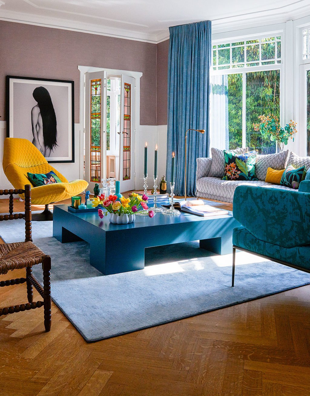 colorful livingroom yellow chair grey and blue sofa purple wallpaper blue table en curtains